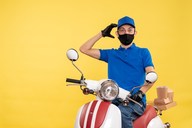 Front view young male courier in blue uniform on yellow background work covid- job delivery service virus bike