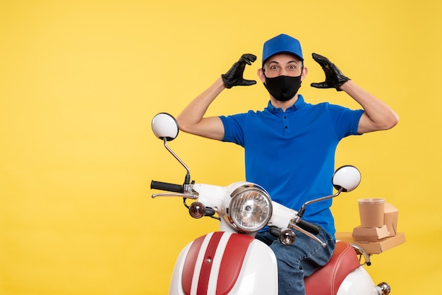 Front view young male courier in blue uniform on the yellow background work covid- job pandemic delivery service virus bike