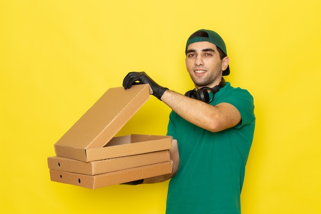 Front view young male courier delivery boxes on yellow