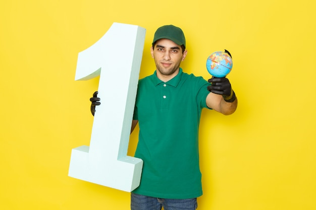 Front view young male courier in green shirt green cap black gloves holding little globe and number one on yellow