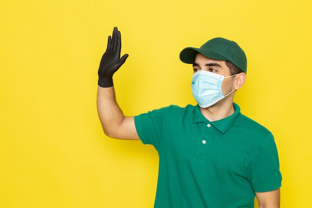 Front view young male courier in green shirt green cap black gloves with raised hand on yellow