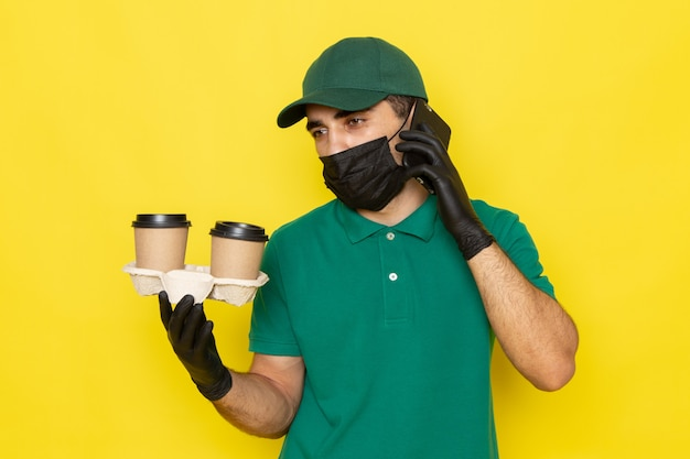 Front view young male courier in green shirt green cap holding coffee cups and talking on phone on yellow
