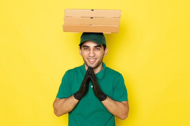 Front view young male courier in green shirt green cap holding delivery boxes on his head with smile on yellow