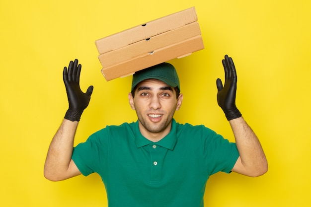 Front view young male courier in green shirt green cap holding delivery boxes with his head in gloves on yellow