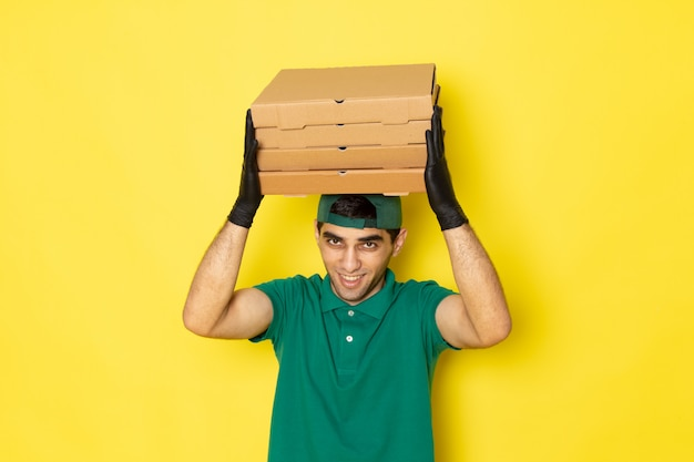 Front view young male courier in green shirt green cap holding delivery boxes with smile on yellow