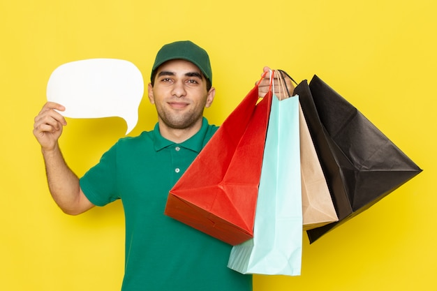 Front view young male courier in green shirt green cap holding shopping packages and white sign on yellow
