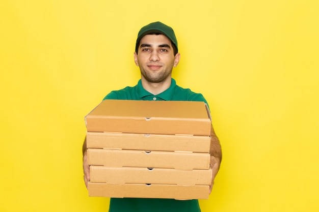 Front view young male courier in green shirt and green cap smiling and holding delivery boxes on yellow