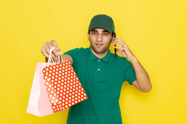 Front view young male courier in green shirt green cap talking on the phone and shopping packages on the yellow background delivering service color