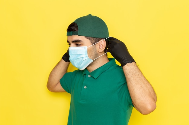 Front view young male courier in green shirt green cap wearing sterile mask on the yellow background delivering service color job