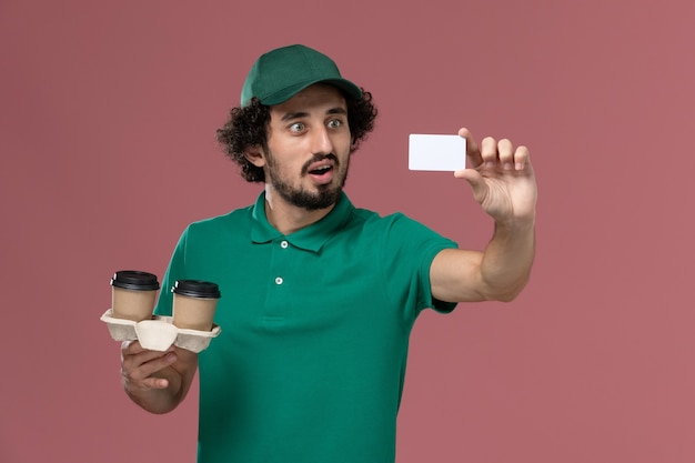Front view young male courier in green uniform and cape holding delivery coffee cups and card on the pink background service job uniform delivery worker male