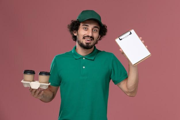 Corriere maschio giovane vista frontale in uniforme verde e mantello che tiene le tazze di caffè di consegna e blocco note sulla consegna uniforme di lavoro di servizio lavoratore maschio sfondo rosa