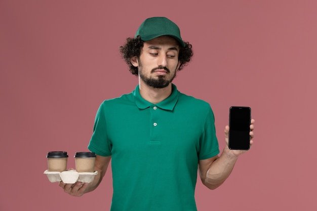 Front view young male courier in green uniform and cape holding delivery coffee cups and phone on the light pink background service job uniform delivery