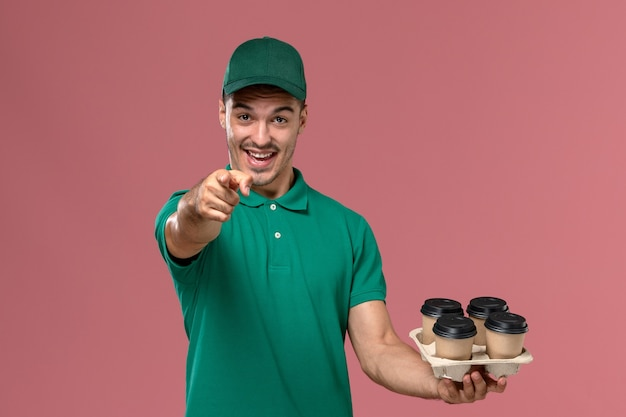 Front view young male courier in green uniform holding brown coffee cups pointing out the camera on pink desk