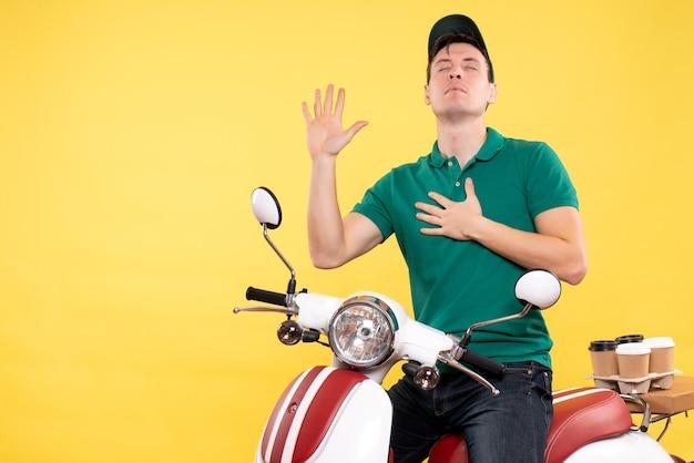 Vista frontale giovane corriere maschio in uniforme verde che prega in bicicletta gialla bike