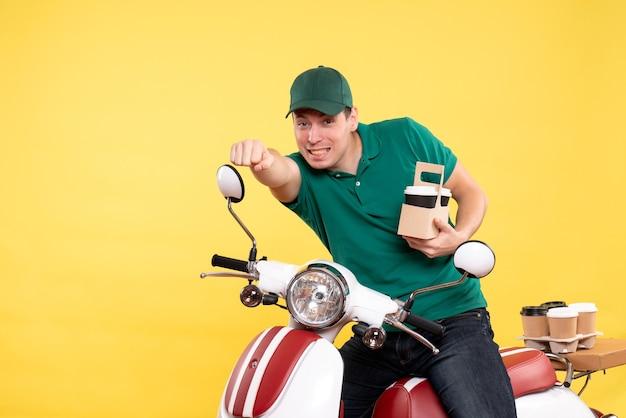 Vista frontale giovane corriere maschio in uniforme verde con caffè su giallo