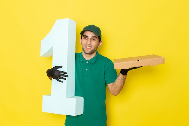 Front view young male courier holding boxes and number one with smile on yellow