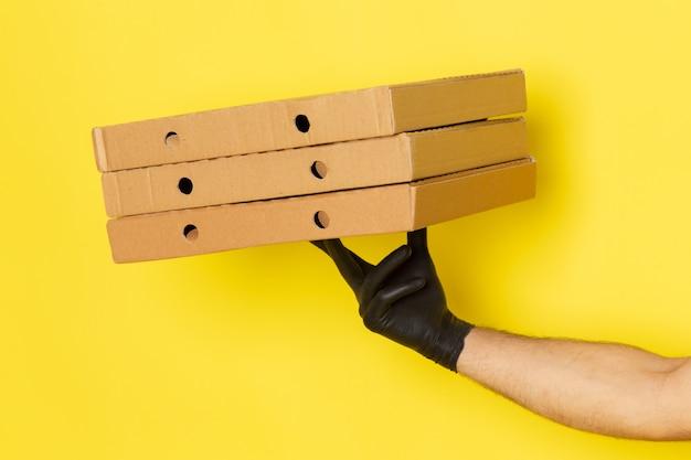 黄色の配達用ボックスを保持している正面の若い男性宅配便