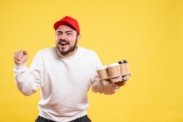 Vista frontale giovane corriere maschio che tiene il caffè di consegna