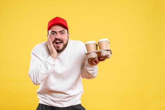 Vista frontale giovane corriere maschio che tiene il caffè di consegna Foto Gratuite