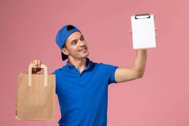 ピンクの壁に彼の手に配達パッケージとメモ帳と青い制服とケープの正面図若い男性の宅配便