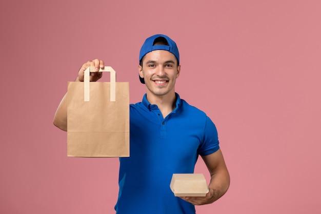 Вид спереди молодой курьер-мужчина в синей форме и плаще с посылками на руках на розовой стене