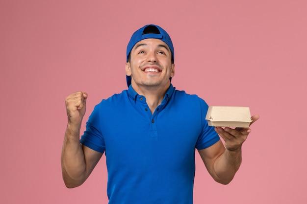 ピンクの壁に配達食品パッケージを保持している青い制服ケープの正面図若い男性宅配便