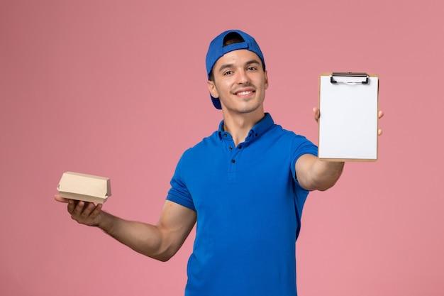 淡いピンクの壁に小さな配達食品パッケージとメモ帳を保持している青い制服ケープの正面図若い男性の宅配便
