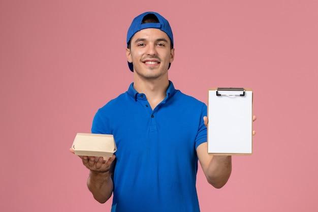 Вид спереди молодой курьер-мужчина в синей форменной накидке с маленьким пакетом еды для доставки и блокнотом, улыбаясь на светло-розовой стене