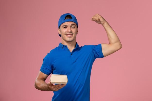 ピンクの壁に曲がる小さな配達食品パッケージを保持している青い制服ケープの正面図若い男性宅配便