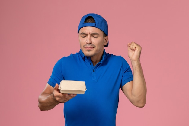 淡いピンクの壁に小さな配達食品パッケージを保持している青い制服ケープの正面図若い男性の宅配便