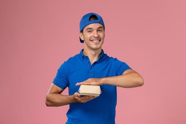 Вид спереди молодой курьер-мужчина в синей форме, держащий маленький пакет с доставкой еды, улыбаясь на розовой стене