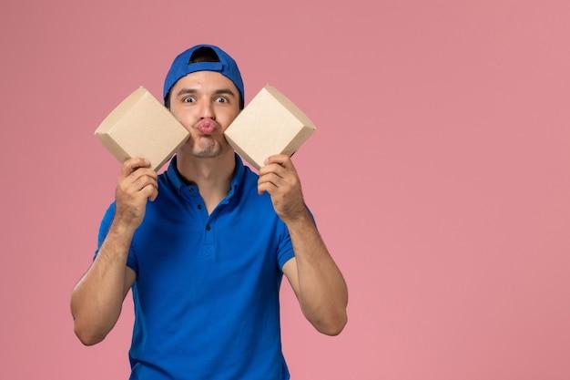 淡いピンクの壁に小さな配達食品パッケージを保持している青い制服の岬の正面図若い男性の宅配便
