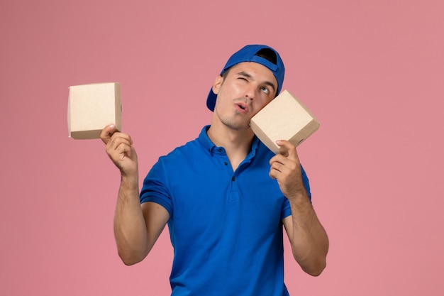 Вид спереди молодой курьер-мужчина в синей форменной накидке с небольшими пакетами еды для доставки на светло-розовой стене