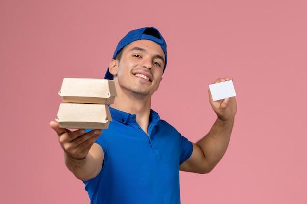淡いピンクの壁にカードと小さな配達食品パッケージを保持している青い制服の岬の正面図若い男性の宅配便