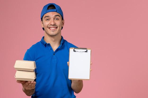 正面図青い制服のケープの若い男性の宅配便は、メモ帳と淡いピンクの壁に微笑んで小さな配達食品パッケージを保持しています