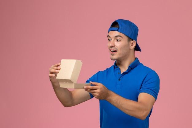 Вид спереди молодой курьер-мужчина в синей форменной накидке с маленьким пустым пакетом еды на розовой стене