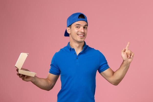 ピンクの壁に笑みを浮かべて少し空の配達食品パッケージを保持している青い制服ケープの正面図若い男性宅配便