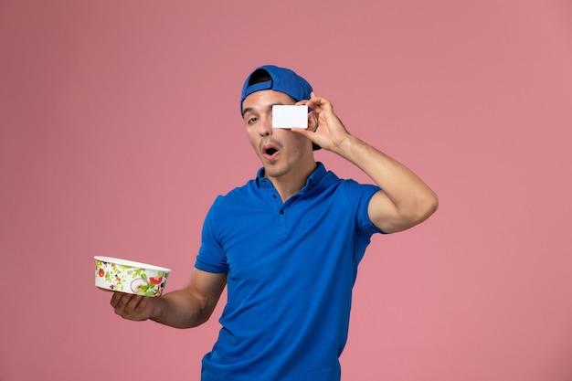 淡いピンクの壁に白いカードと丸い配達ボウルを保持している青い制服ケープの正面図若い男性宅配便