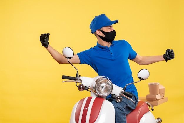 黄色の背景に青い制服の正面図若い男性宅配便