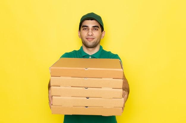 Вид спереди молодой курьер-мужчина в зеленой рубашке и зеленой кепке улыбается и держит коробки для доставки на желтом