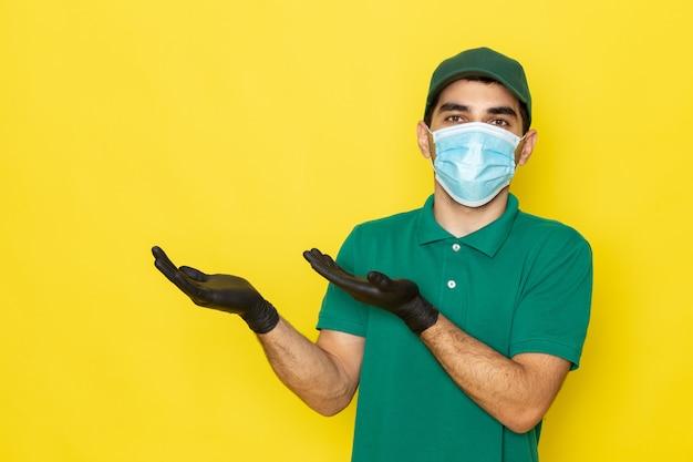Вид спереди молодой мужчина-курьер в зеленой рубашке зеленая кепка черные перчатки с поднятыми руками на желтом