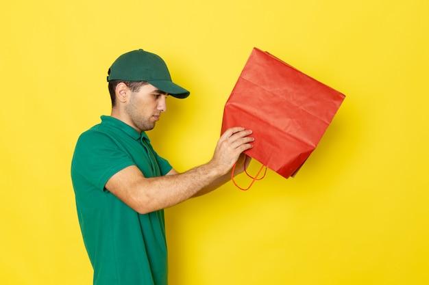 黄色のショッピングパッケージをチェックする緑のシャツグリーンキャップの正面の若い男性宅配便