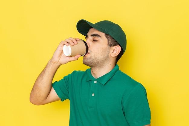 Вид спереди молодой мужчина-курьер в зеленой рубашке с зеленой кепкой, пьющий кофе на желтом