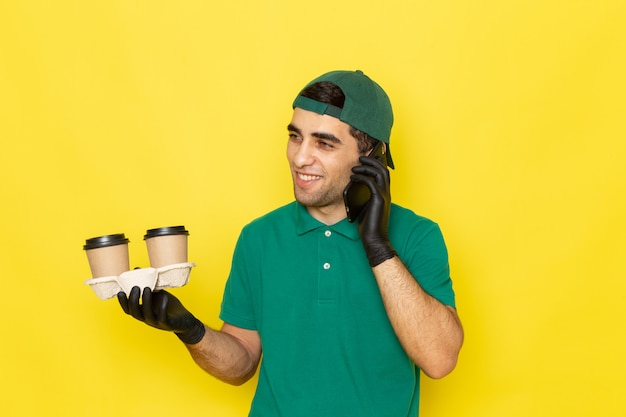 Вид спереди молодой курьер-мужчина в зеленой рубашке с зеленой кепкой держит кофейные чашки и разговаривает по телефону на желтом