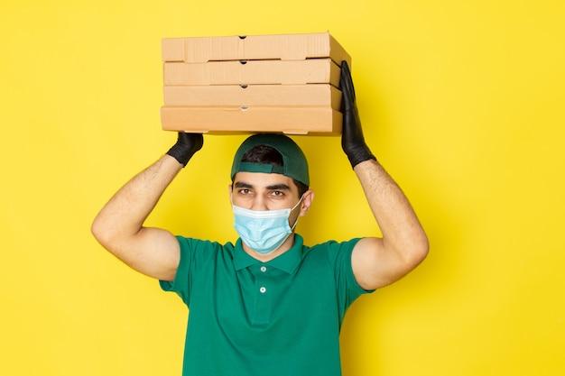 黄色の彼の頭の上の配信ボックスを保持している緑のシャツグリーンキャップの正面の若い男性宅配便