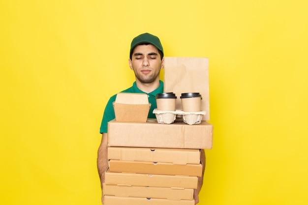 黄色の配達用ボックスとコーヒーカップを保持している緑のシャツグリーンキャップの正面の若い男性宅配便