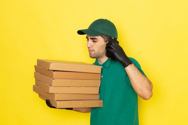 Вид спереди молодой мужчина-курьер в зеленой рубашке с зеленой кепкой держит коробки для доставки и разговаривает по телефону на желтом