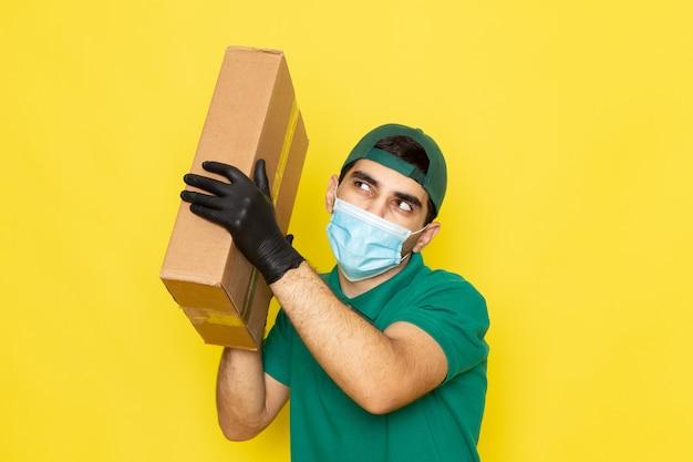 黄色のフードボックスを保持している緑のシャツグリーンキャップの正面の若い男性宅配便