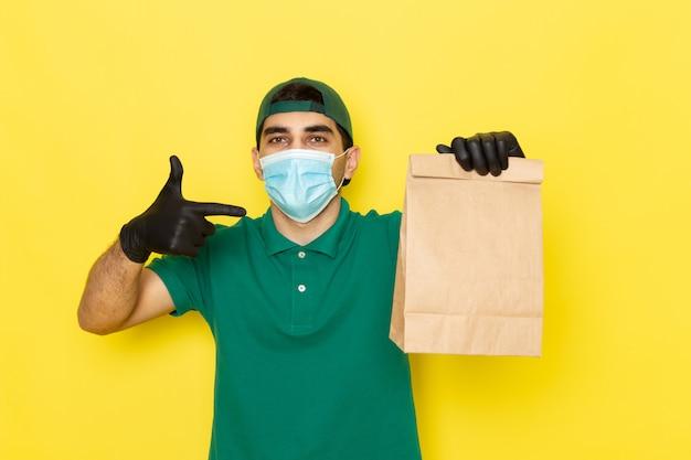 黄色のマスクを着て食品パッケージを保持している緑のシャツグリーンキャップの正面の若い男性宅配便
