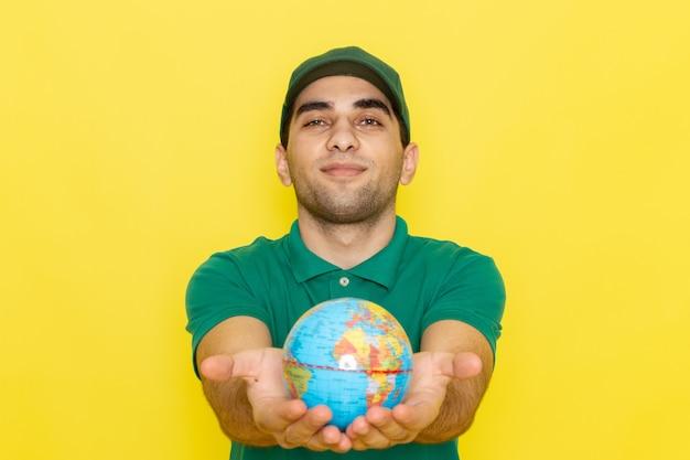 Вид спереди молодой курьер-мужчина в зеленой рубашке с зеленой кепкой держит глобус на желтом